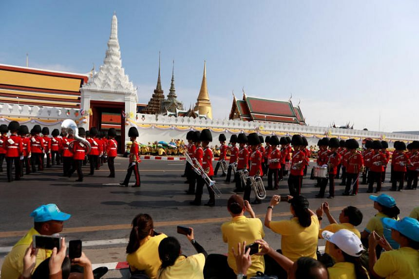 Well-wishers gather along the 7km royal procession route, all wearing yellow, the colour associated with the king.