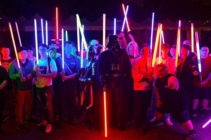Star Wars fans with model lightsabres during an event to promote the upcoming unofficial Star Wars Day in Taipei.