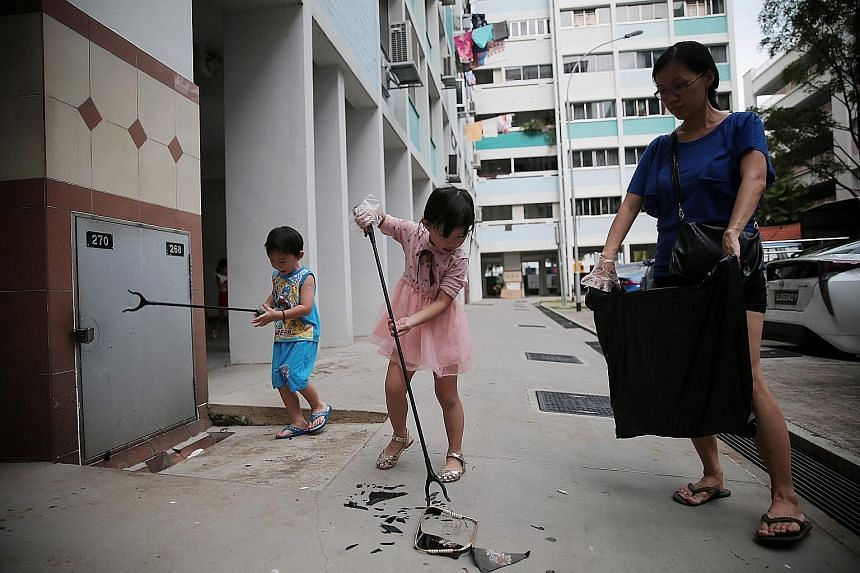 Siblings Aiden Wong, five, (left) and Averie Wong, six, and their mother, Madam Jenny Ong, 39, picking up litter during No Cleaners Day at Nee Soon South yesterday.