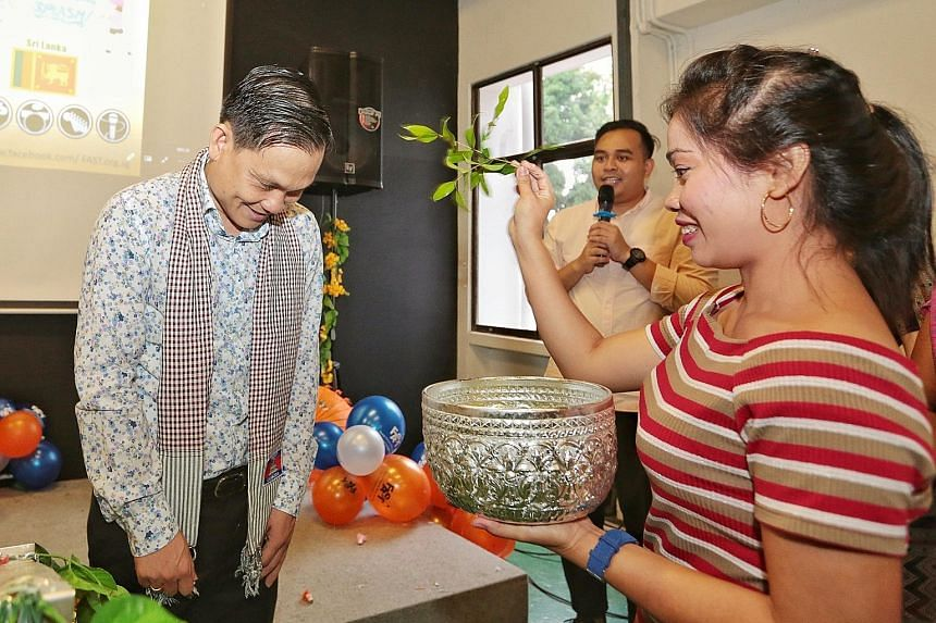 Ms Iek Saron, a Cambodian domestic helper, sprinkling water as a blessing on Cambodian Ambassador to Singapore Ngoun Sokveng. The MC for the event was Mr Nizam Amlan of non-profit group Fast.