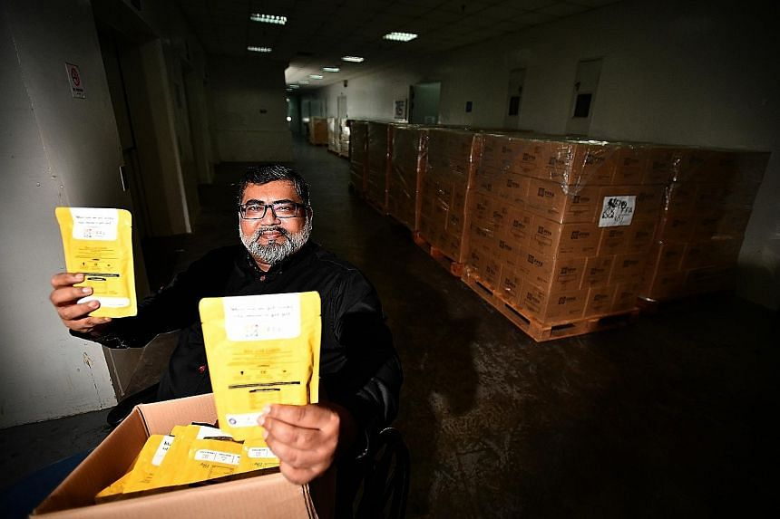 Free Food For All founder Nizar Mohamed Shariff showing some of the ready-to-eat local meals in retort pouches. Behind him are cartons containing the food packages. The charity will be delivering 800 of such cartons to 800 needy households during Ram
