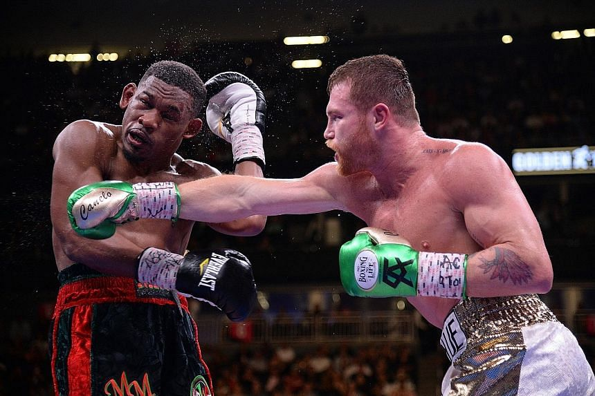 """Saul """"Canelo"""" Alvarez landing a punch on Daniel Jacobs during their WBC/WBA/IBF middleweight unification world championship boxing bout at the T-Mobile Arena on Saturday night. PHOTO: REUTERS"""
