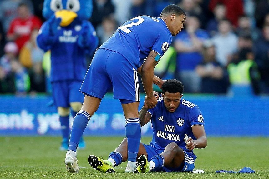 Cardiff City's Lee Peltier consoling a dejected Nathaniel Mendez-Laing after their 3-2 defeat by Crystal Palace, sealing their relegation from the Premier League. PHOTO: REUTERS