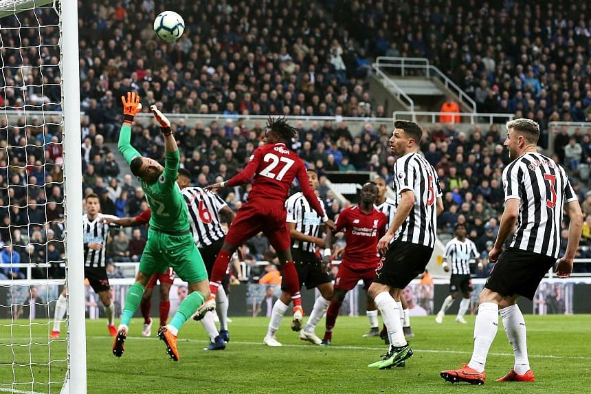 Substitute Divock Origi heading home against Newcastle to give Liverpool the lead late in the game. The Reds won 3-2 to take their race with Manchester City for the Premier League title to the season's final weekend. PHOTO: EPA-EFE