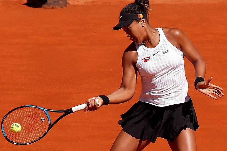 Naomi Osaka hitting a return against Dominika Cibulkova in the first round of the Madrid Open yesterday. The Japanese won in straight sets and will next face Spain's Sara Sorribes Tormo. PHOTO: EPA-EFE