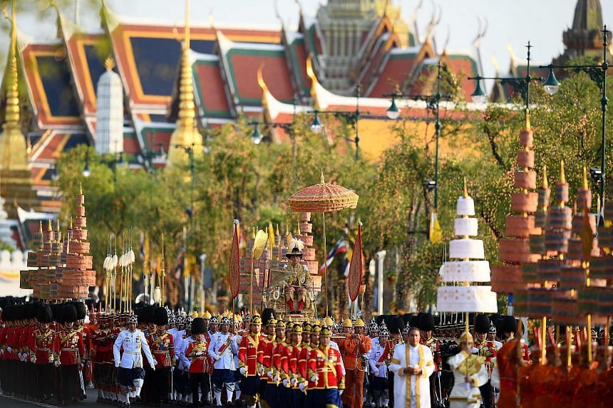 Thai King Maha Vajiralongkorn, wearing a golden robe and a ceremonial feathered hat, being carried on a palanquin during the procession in Bangkok yesterday.