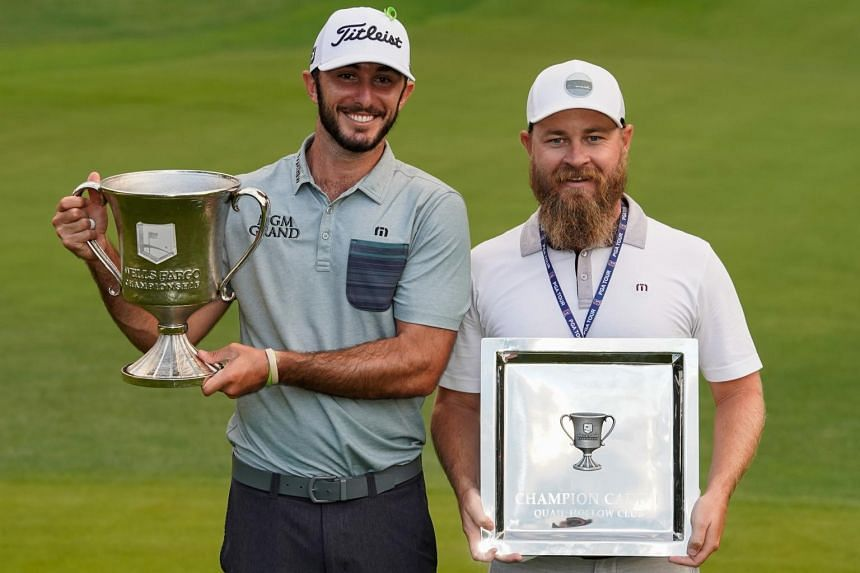 Max Homa (left) and caddie Joe Ryder hold their trophies after the final round of the Wells Fargo Championship golf tournament at Quail Hollow Club on May 5, 2019.