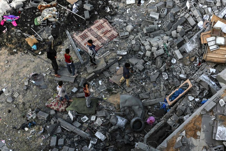 Palestinian children gathering among the rubble of a building that was destroyed during Israeli air strikes on Gaza City.