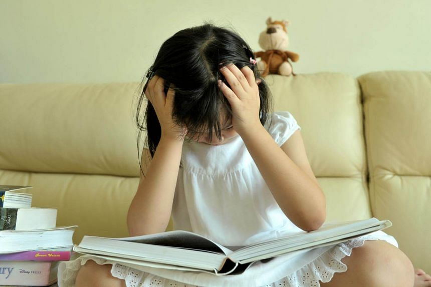 Posed photo of a child reading a book.
