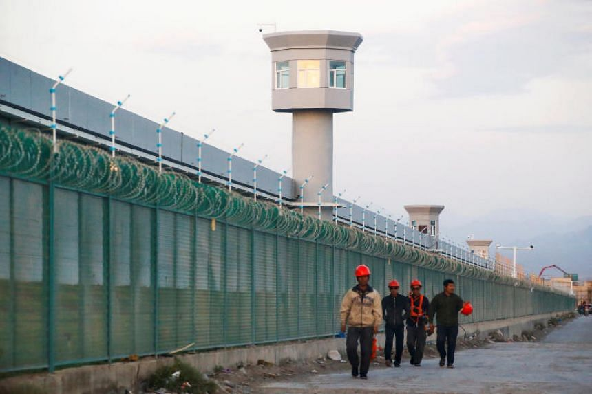 Workers by the perimeter fence of a vocational skills education centre in Dabancheng in Xinjiang Uighur Autonomous Region, China.