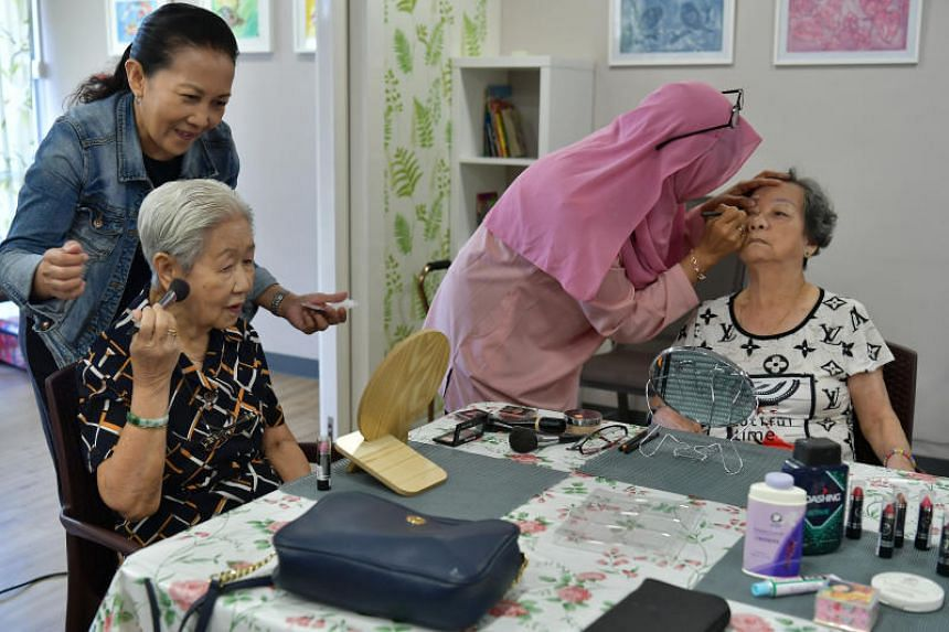 Madam Tay Ah Lay (left), 83, and Madam Tay Yeok Leng (right), 83, getting their make-up done with the help of St Luke staff member Anita Conriana (left) and volunteer Aslinda Jambari. Some of the make-up used are from the Heritage Trunks.
