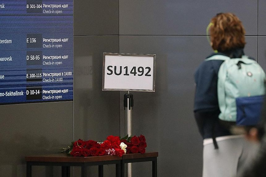 The plane caught fire as it struck the runway a second time and then skidded along the runway with its nose angled upward, with the engines scraping the ground and flames streaking out behind. (Below) Flowers placed by the information board at the ai