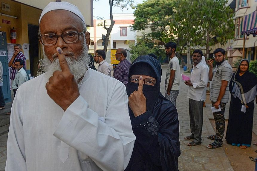 An elderly Indian Muslim couple displaying their ink-marked fingers after casting their votes in Chennai on April 18 during the second phase of the Indian elections. Indian Prime Minister Narendra Modi gesturing to supporters as he arrived to file hi