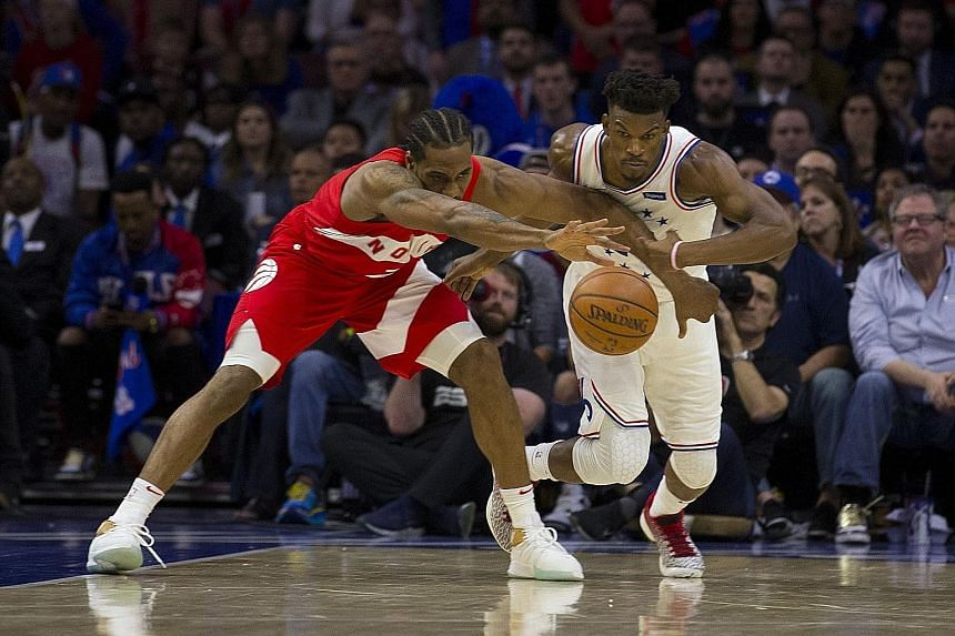 The Raptors' Kawhi Leonard and the 76ers' Jimmy Butler fighting for the ball in Toronto's 101-96 win in Philadelphia on Sunday. PHOTO: AGENCE FRANCE-PRESSE