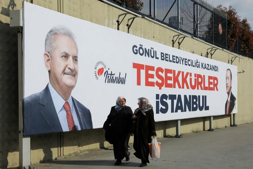 People walk past AK Party billboards with pictures of Turkish President Tayyip Erdogan and mayoral candidate Binali Yildirim in Istanbul, Turkey, on April 1, 2019.
