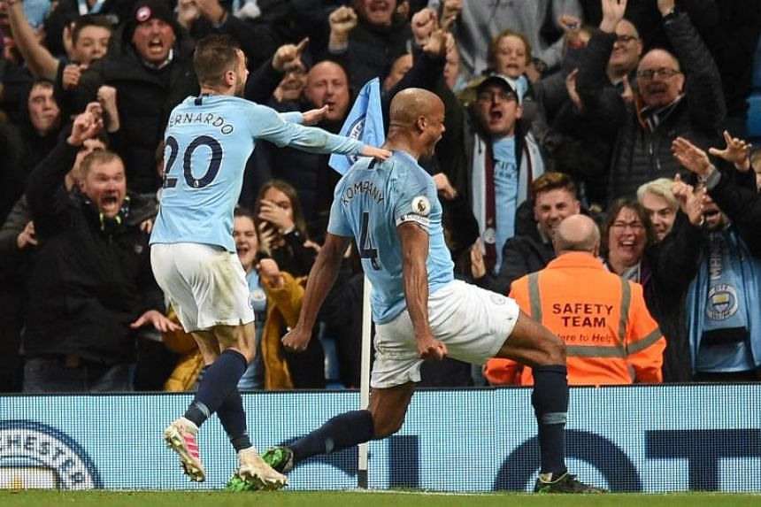 Manchester City's Belgian defender Vincent Kompany (right) celebrates scoring the opening goal during the match between Manchester City and Leicester City at the Etihad Stadium in Manchester, north west England, on May 6, 2019.