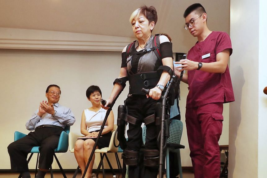 Ms Teresa Tan walking on stage with the aid of an exoskeleton suit and a hospital staff member at the launch of the Temasek Foundation - Improving Mobility via Exoskeletons (iMOVE) programme at Alexandra Hospital yesterday. With them are fellow iMOVE