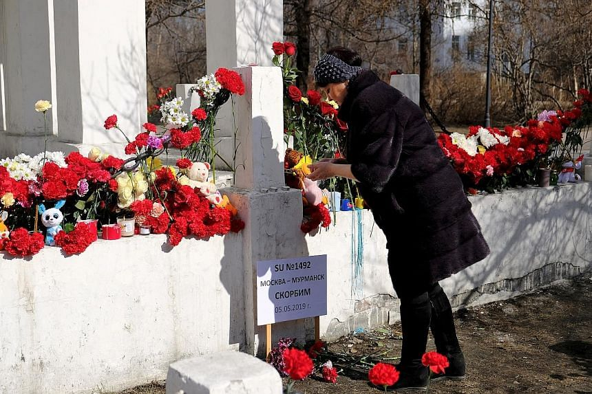 A woman at a makeshift memorial in Murmansk, Russia, dedicated to the victims of Sunday's Aeroflot crash that killed at least 40 people. PHOTO: REUTERS