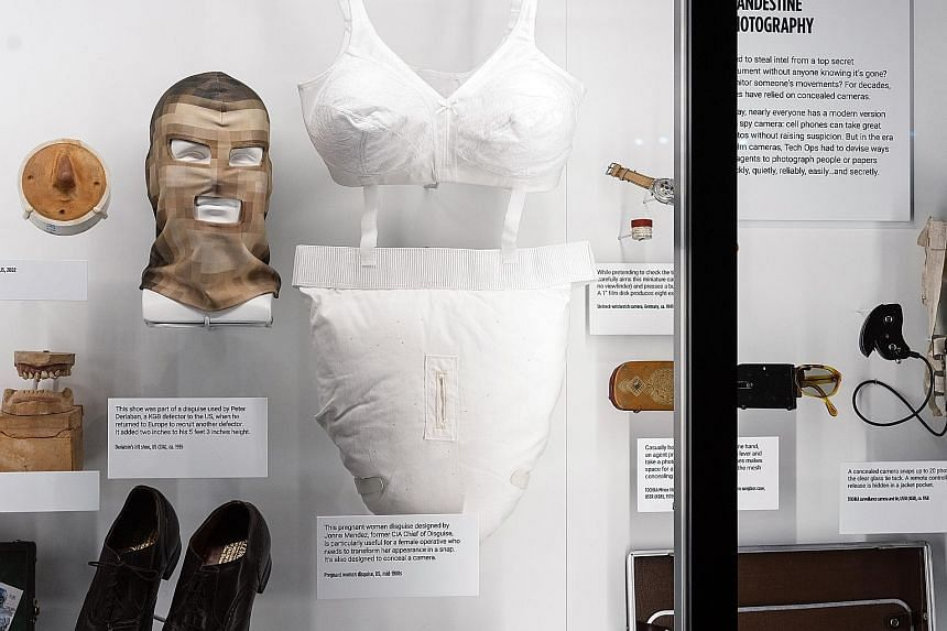 Clockwise from above left: An exhibit on the assassination of Russian revolutionary Leon Trotsky; an East German microdot message in a hollow tooth; and a fake pregnancy suit from the mid-1980s and other disguises.