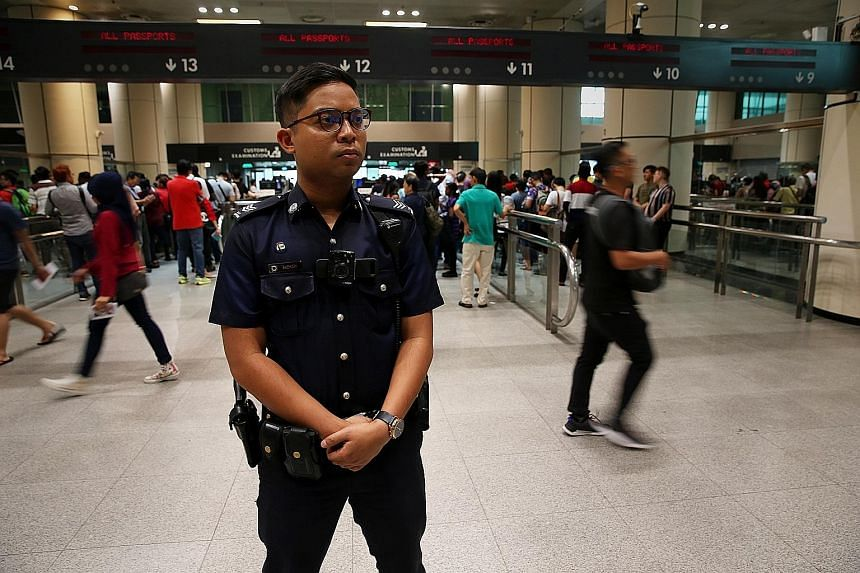 Sergeant Salehudin Samsudin (left) has to be alert at all times. Recently, he spotted a suspicious-looking man who turned out to be travelling under multiple identities.