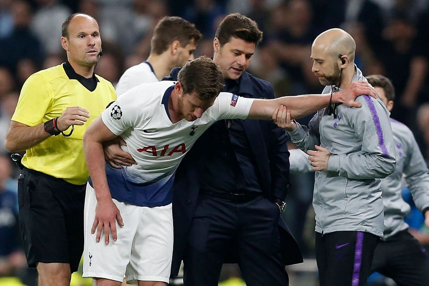 Spurs coach Mauricio Pochettino (second right) helps Vertonghen (centre) as he leaves the pitch.