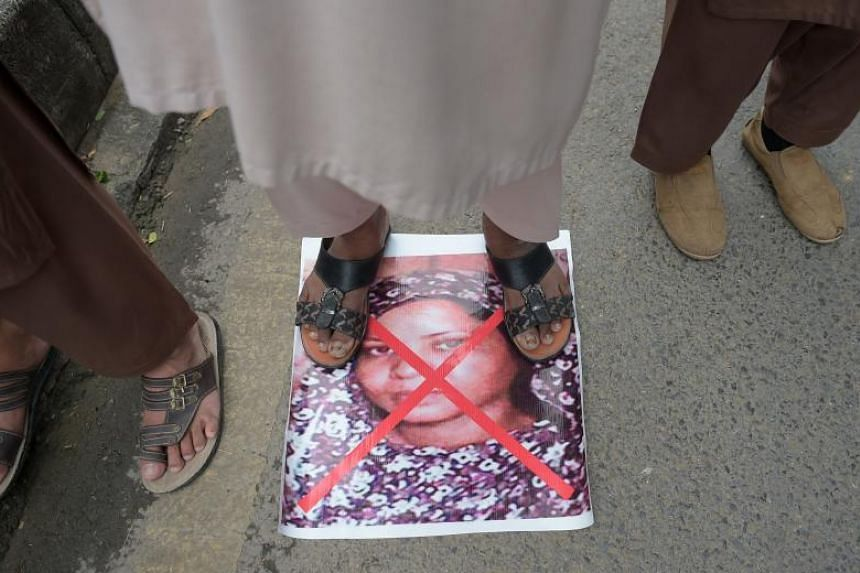 A Pakistani supporter of hardline religious party Ahle Sunnat Wal Jamaat stands on an image of Christian woman Asia Bibi as they march during a protest rally following the Supreme Court's acquittal of Ms Bibi, in Islamabad on Nov 2, 2018.