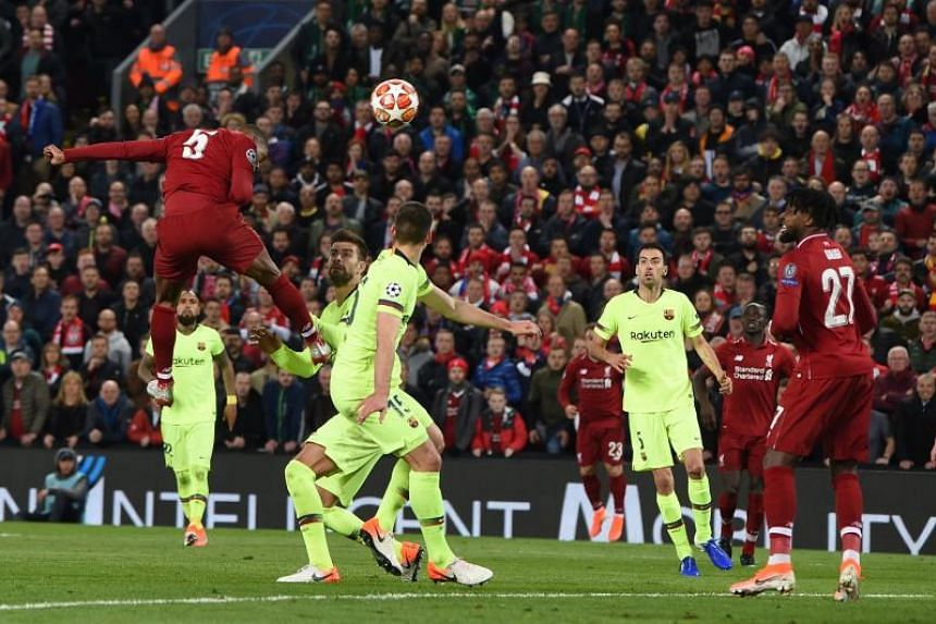 Liverpool midfielder Georginio Wijnaldum (left) heads the ball to score their third goal during the UEFA Champions league semi-final second leg football match between Liverpool and Barcelona at Anfield in Liverpool, England on May 7, 2019.