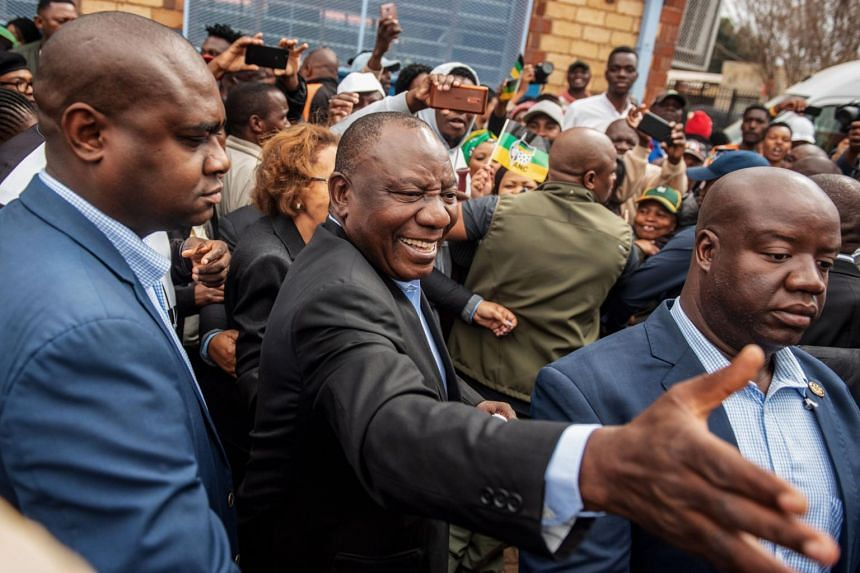 President of South Africa and the African National Congress Cyril Ramaphosa (centre) greets voters as he arrives to cast his vote for the general elections at the Hitekani Primary School, in Chiawelo, Soweto, on May 8, 2019.
