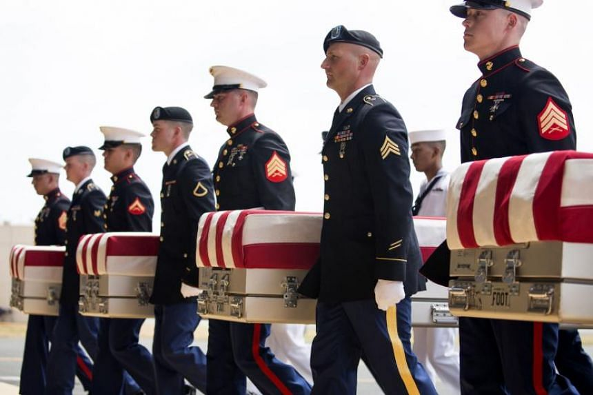 US military personnel carry the remains of Korean War soldiers at Hangar 19, Joint base Pearl Harbor Hickam in Honolulu, Hawaii, on Aug 1, 2018.