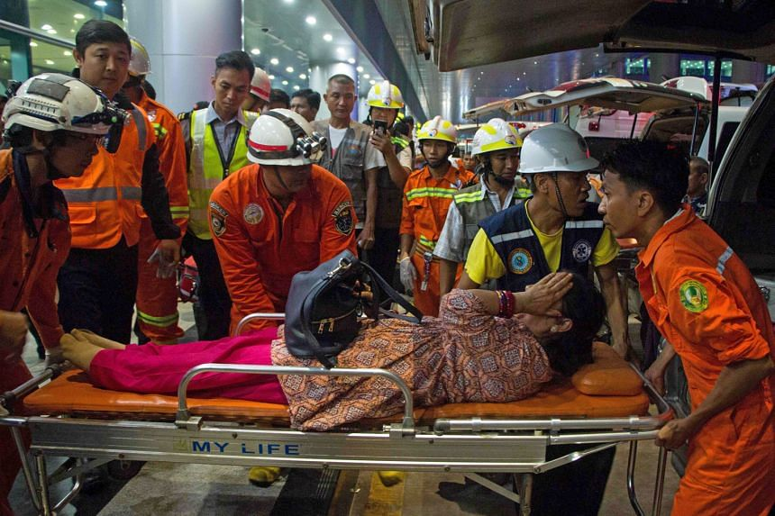Rescue workers transporting an injured woman who was on board the Biman Bangladesh Airlines flight yesterday. The plane slid off the runway when a storm hit the city.
