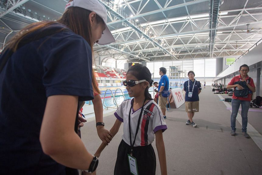 Radin Mas Primary School pupil Preetika Riona trying out blackened goggles for visually impaired students on Tuesday at the OCBC Aquatic Centre. She is one of over 50 students from Radin Mas and Bukit Panjang Government High who attended a learning j