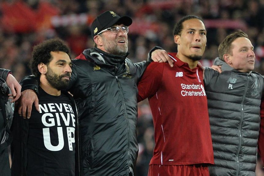 Liverpool's head coach Jurgen Klopp and players Mohamed Salah (left) and Virgil van Dijk celebrate after winning the Champions League semi-final second leg match against Barcelona in Liverpool on May 7, 2019.