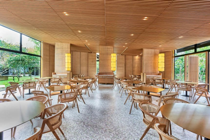 The dining room of Min Jiang at Dempsey is lit by sunlight filtering in through floor-to-ceiling glass walls during the day.