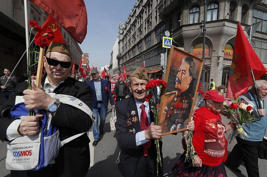Russian communists taking part in a demonstration in Moscow yesterday, as the country marked the 74th anniversary of the victory over Nazi Germany in World War II. The annual event involves a parade that sees military hardware, including tanks and in
