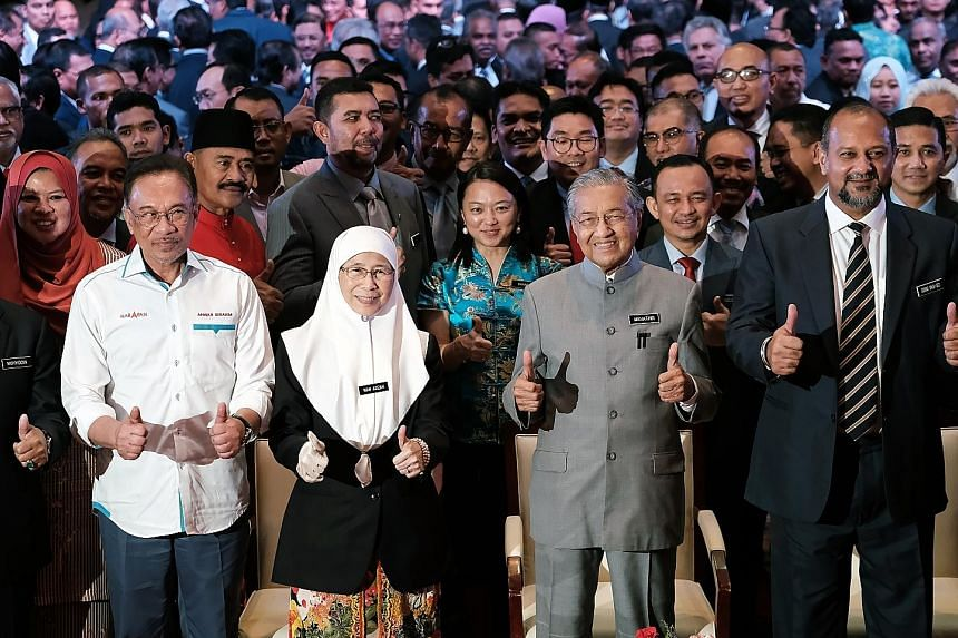 From far left: Datuk Seri Anwar Ibrahim, Malaysia's premier-in-waiting, Deputy Prime Minister Wan Azizah Wan Ismail, Prime Minister Mahathir Mohamad, and Communications and Multimedia Minister Gobind Singh Deo making the thumbs-up gesture at yesterda