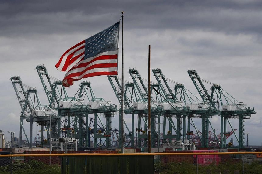 The US flag flying over shipping cranes in Long Beach, California. Experts say that while the trade war is gruelling and could become worse, the US has the upper hand.