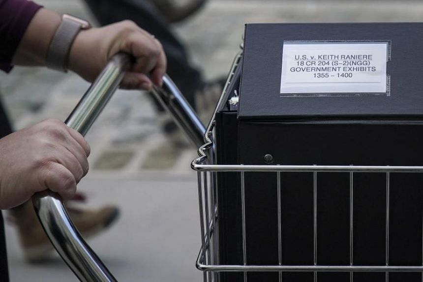 Staff from the prosecution team push carts full of court documents related to the US v. Keith Raniere case as they arrive at the US  District Court for the Eastern District of New York, on May 7, 2019