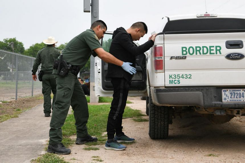 A US Border Patrol agent searches an undocumented migrant who illegally crossed the Rio Grande in Los Ebanos, Texas, US, on April 6, 2019.