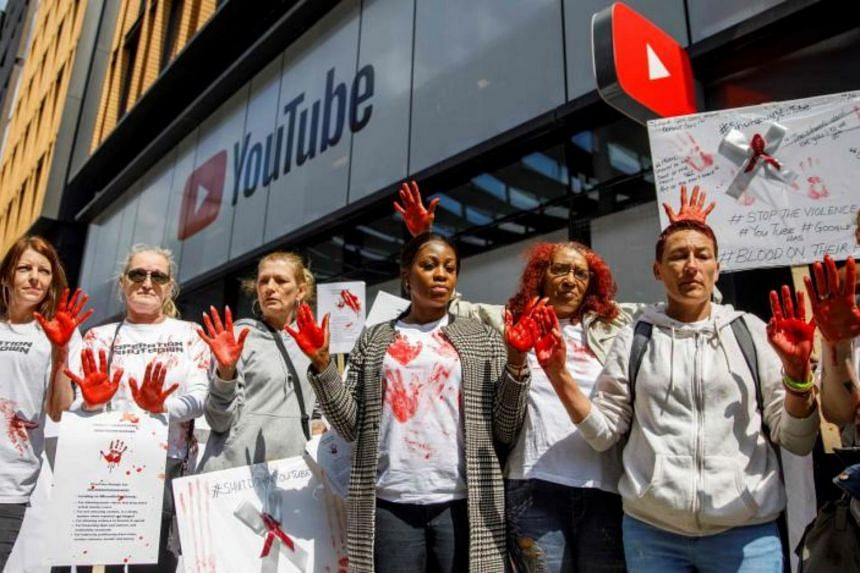 Anti-knife crime activists, with their hands painted red to represent blood, demonstrate outside the UK offices of YouTube in London on May 10, 2019.