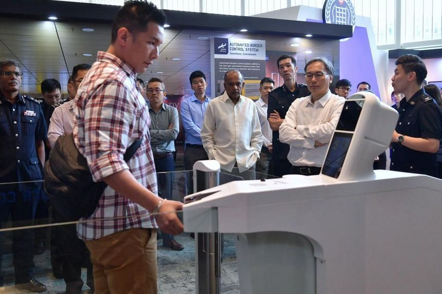 Law and Home Affairs Minister K. Shanmugam (centre) viewing a mock-up of an automated lane of the Automated Border Control System at the University Cultural Centre, on May 10, 2019.