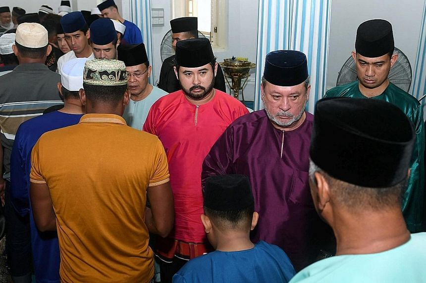 Johor's Sultan Ibrahim Sultan Iskandar (in purple) and his son, Tunku Ismail Sultan Ibrahim (in red), greeting Muslims after Hari Raya prayers at a mosque last June. The war of words between Malaysian Prime Minister Mahathir Mohamad and the Johor roy