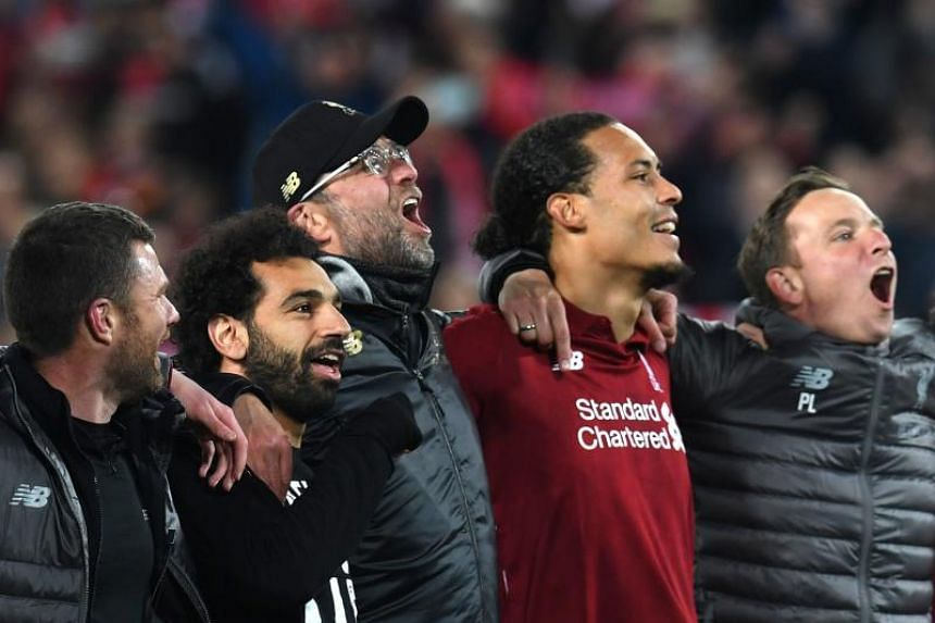 Liverpool's Egyptian midfielder Mohamed Salah (second from left), Liverpool's German manager Jurgen Klopp (C) and Liverpool's Dutch defender Virgil van Dijk celebrate after winning the UEFA Champions league semi-final second leg football match betwee