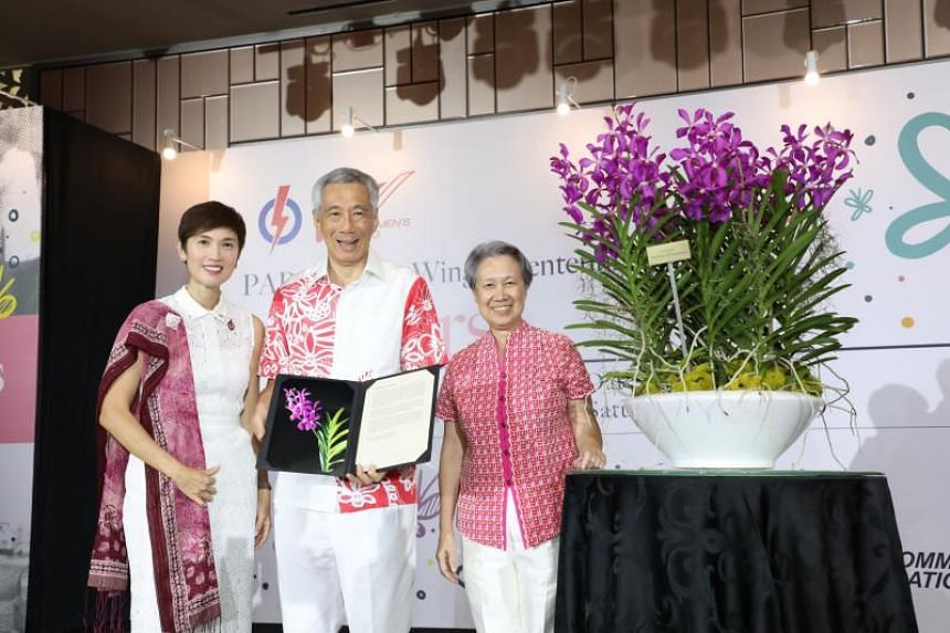 """Minister for Manpower and the People's Action Party's Women's Wing chairman Josephine Teo, Prime Minister Lee Hsien Loong and his wife Ho Ching with an orchid named """"Aranda Mothers of Singapore"""", unveiled at the PAP Women's Wing Bicentennial Tribute"""
