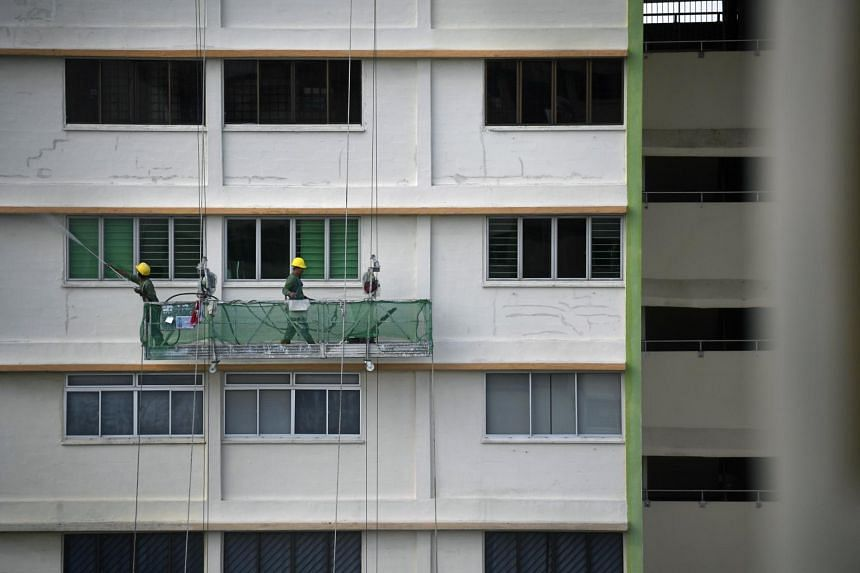 Workers on a gondola washing the walls of the facade of the HDB flat to prepare for a freshcoat of paint as part of the the Home Improvement Programme or upgrading of the HDB flats at Toa Payoh Lorong 8, on Oct 21, 2018.