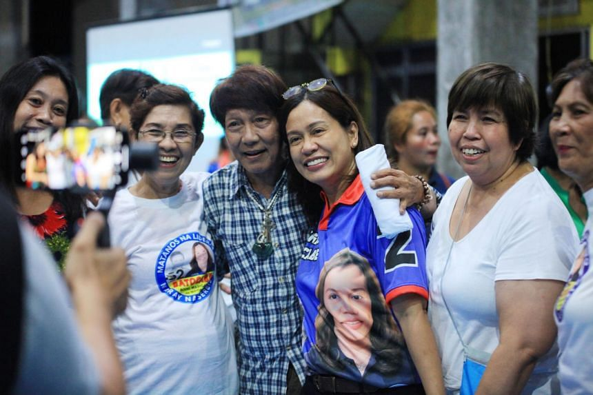 Politician Gertrudes Batocabe (centre, in bright blue), wife of the late congressman Rodel Batocabe, poses for photos with supporters during a campaign rally in Daraga, south of Manila on April 30, 2019.