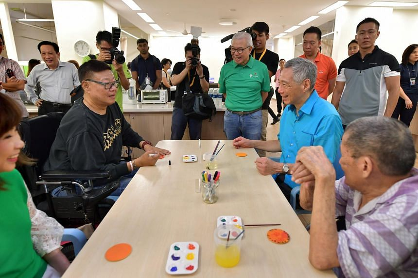 Prime Minister Lee Hsien Loong chats with short-stay unit resident Kevin Tan, 52, at the official opening of Ren Ci's Ang Mo Kio nursing home on May 11, 2019.