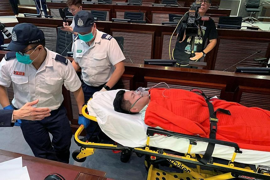 Pro-democracy lawmaker Gary Fan being carried away on a stretcher yesterday after he collapsed during clashes between the two rival camps. Pro-democracy lawmakers clashing with their pro-Beijing counterparts yesterday, with both sides fighting for co