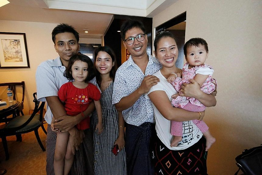 Mr Wa Lone (in glasses) with his wife, Ms Pan Ei Mon, and their daughter, and Mr Kyaw Soe Oo with his daughter and his wife, Ms Chit Su Win, last Tuesday. The two Reuters journalists were freed from prison that day after a presidential amnesty.