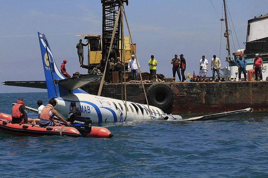 Members of the Friends of Zira Island and Sidon's Beach association submerging an old civil aircraft in the Mediterranean, near the island of Zira, around 600m off the shore of the southern Lebanese city of Sidon, yesterday. A number of planes as wel