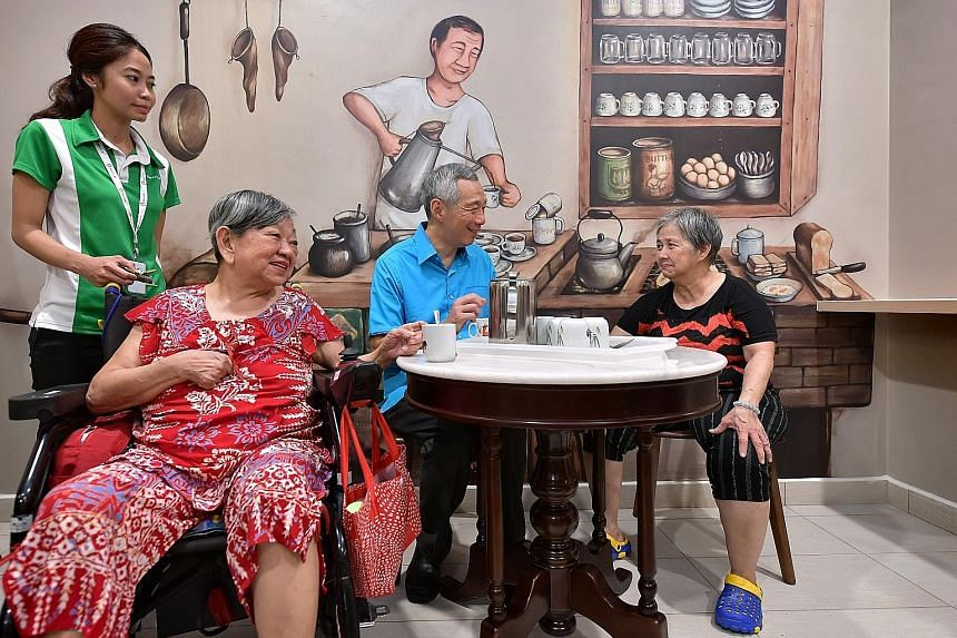 Prime Minister Lee Hsien Loong chatting with nursing home residents Chew Eng Huay (seated far left), 73, and Hea Eng, 59, at the official opening of Ren Ci @ Ang Mo Kio Nursing Home yesterday.